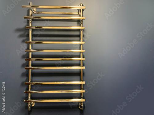 Chrome heated towel rail on a blue wall, warm light Fototapeta