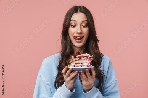 Stampa su Tela Image of surprised young woman liking her lips while holding cake