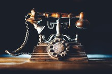Close-up Of Vintage Rotary Phone On Table Against Black Background