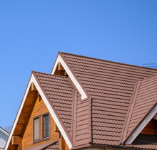 Gable Triangular Roof With A Large Pediment. Glued Beams With Grooves, Attic Window, Brown Tiles. Blue Sky Background.
