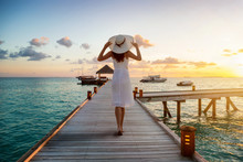 A Beautiful Tourist Woman In White Dress On Summer Vacations Walks Over A Wooden Pier Into The Tropical Sunset On The Maldives Islands