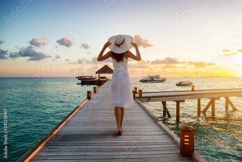 Fotografía A beautiful tourist woman in white dress on summer vacations walks over a wooden