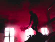 Low Angle View Of Silhouette Man Holding Smoke Bomb In Abandoned Building