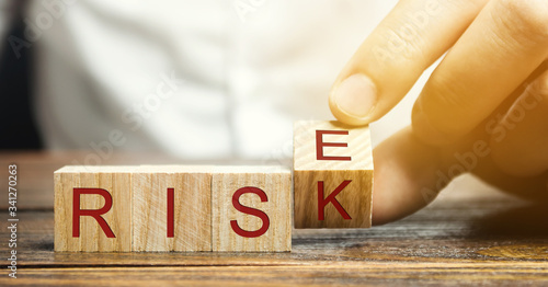 Businessman changes wooden blocks with the words Risk and Rise Canvas Print