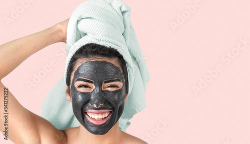 Obraz na plátně Happy smiling girl applying facial black mask - Young woman having skin care cle