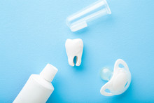 White Tooth, Tube Of Toothpaste, Soother And Transparent Silicone Fingertip Toothbrush On Light Blue Table Background. Pastel Color. Babies Teeth Hygiene. Closeup. Top Down View.