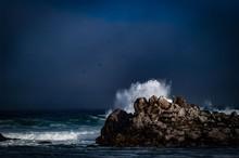 Waves Breaking Against Rocks In Sea Against Sky