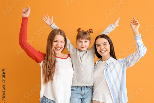 Photo Happy lesbian couple with little adopted girl on color background
