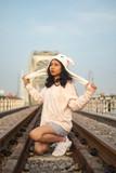 Fototapeta Londyn - A young beautiful girl poses on an old bridge.