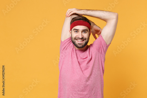 Funny young bearded fitness sporty guy sportsman in headband t-shirt spend weekend in home gym isolated on yellow background Tablou Canvas