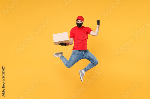 Fototapeta Fun jumping delivery man in red cap t-shirt uniform sterile face mask gloves isolated on yellow background studio Guy employee courier Service quarantine pandemic coronavirus virus 2019-ncov concept. obraz na płótnie