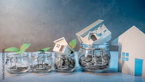 Fototapeta Saving money for retirement. Property or real estate investment. Home mortgage loan rate. Coins, dollar banknotes, credit card and house model in glass jars on the table. Financial growth concept obraz