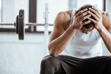 Upset Sportsman Touching Head While Sitting Near Barbell In Gym