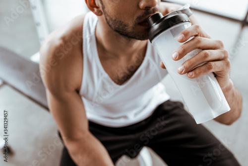 Fotografia cropped view of sportsman drinking protein milkshake while holding sports bottle