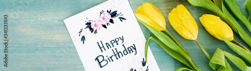 Fototapeta panoramic shot of greeting card with happy birthday lettering near yellow tulips