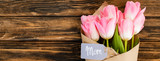 panoramic shot of tag with mom lettering on pink tulips wrapped in paper on wooden surface, mothers day concept