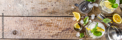 Boozy lemon basil lemonade, with fresh basil leaves, lemons and crushed ice, rustic wooden background copy space