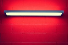 Low Angle View Of Illuminated Lighting Equipment On Red Brick Wall