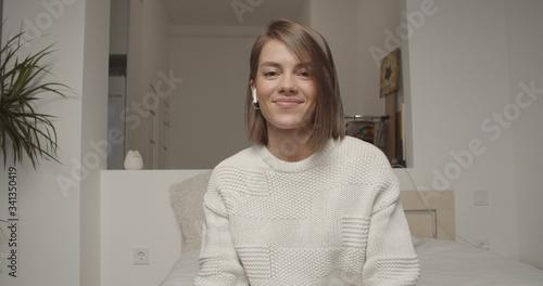 Fototapeta Smiling young woman blogger influencer doing videochat obraz