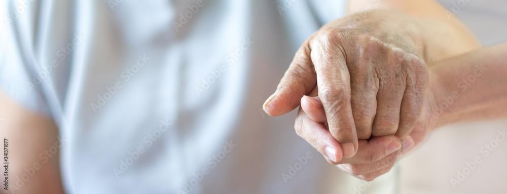 Fototapeta Caregiver, carer hand holding elder hand in hospice care background. Philanthropy kindness to disabled old people concept.Happy mother's day.