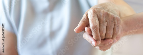 Obraz Caregiver, carer hand holding elder hand in hospice care background. Philanthropy kindness to disabled old people concept.Happy mother's day. - fototapety do salonu