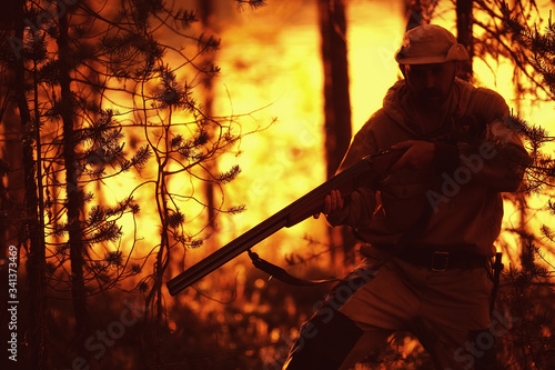 hunting man / hunter with a gun hunting in the autumn forest, yellow trees lands Canvas Print