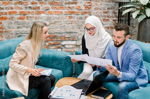Fototapety, obrazy: Business, people and teamwork concept. Multiethnic focused business team, Caucasian man and woman, Muslim woman working with project financial papers meeting in modern office room