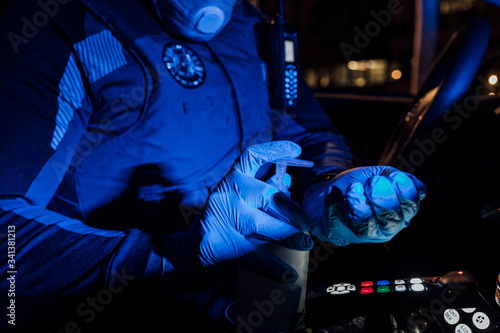 Fotografie, Tablou Policeman wearing mask, protective gloves and using sanitizer during emergency m