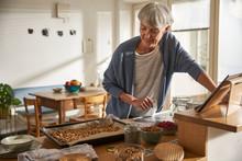 Senior Woman Preparing Granola In Kitchen