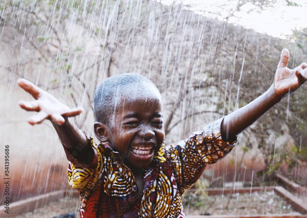 Fototapeta African Black Boy Cheerful So Unbelievably Happy to get Water from Rain in Dry Season
