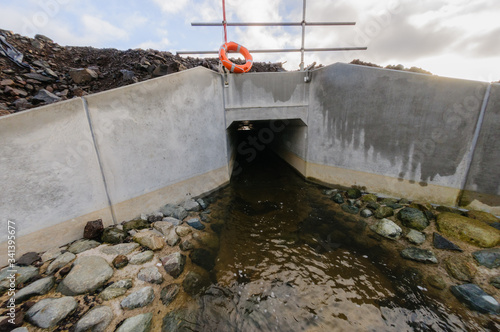 Valokuvatapetti Concrete culvert diverting a small stream underneath a newly constructed road