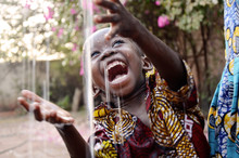 Incredibly Happy African Child Enjoying The Rain As A Water Scarcity Symbol