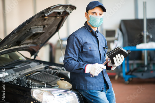 Masked car mechanic holding a jug of motor oil, coronavirus work concept
