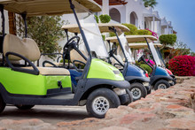 Several Golf Cars Are Parked In The Parking Lot. Electric Cars For Moving Around The Resort Complex Of A Five-star Hotel. A Means Of Transportation For Tourists.