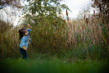 A Child Playing In The Park Alone Near A Pond Or Lake