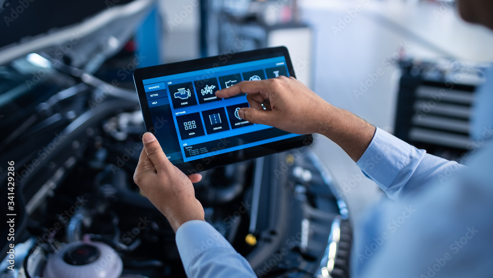 Fototapeta Car Service Manager or Mechanic Uses a Tablet Computer with a Futuristic Interactive Diagnostics Software. Specialist Inspecting the Vehicle in Order to Find Broken Components In the Engine Bay.