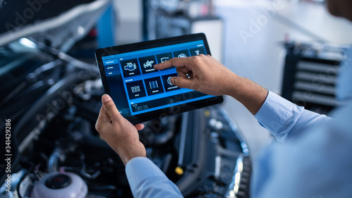 Obraz na plátně Car Service Manager or Mechanic Uses a Tablet Computer with a Futuristic Interactive Diagnostics Software