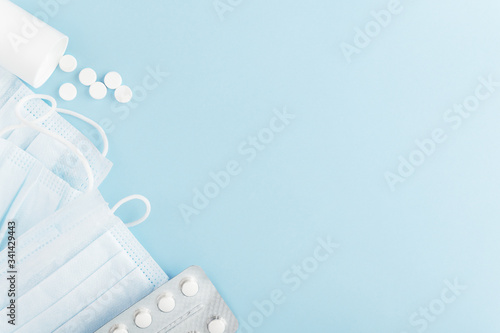 Fototapeta Personal hygiene products for human on backdrop. Medical protective mask and scattered tablets on light background. Mockup, copy space on right side. Health and hygiene concept. Isolated on blue obraz na płótnie