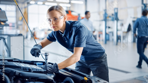 Fototapeta Beautiful Empowering Female Mechanic is Working on a Car in a Car Service. Woman in Safety Glasses is Fixing the Engine. She's Using a Ratchet. Modern Clean Workshop with Cars.  obraz