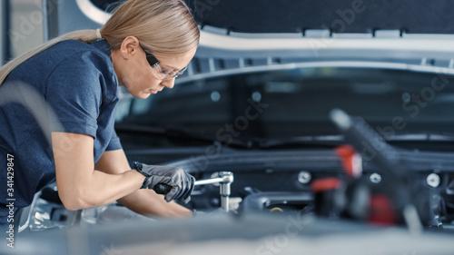 Fotografie, Obraz Portrait Shot of a Female Mechanic Working on a Vehicle in a Car Service