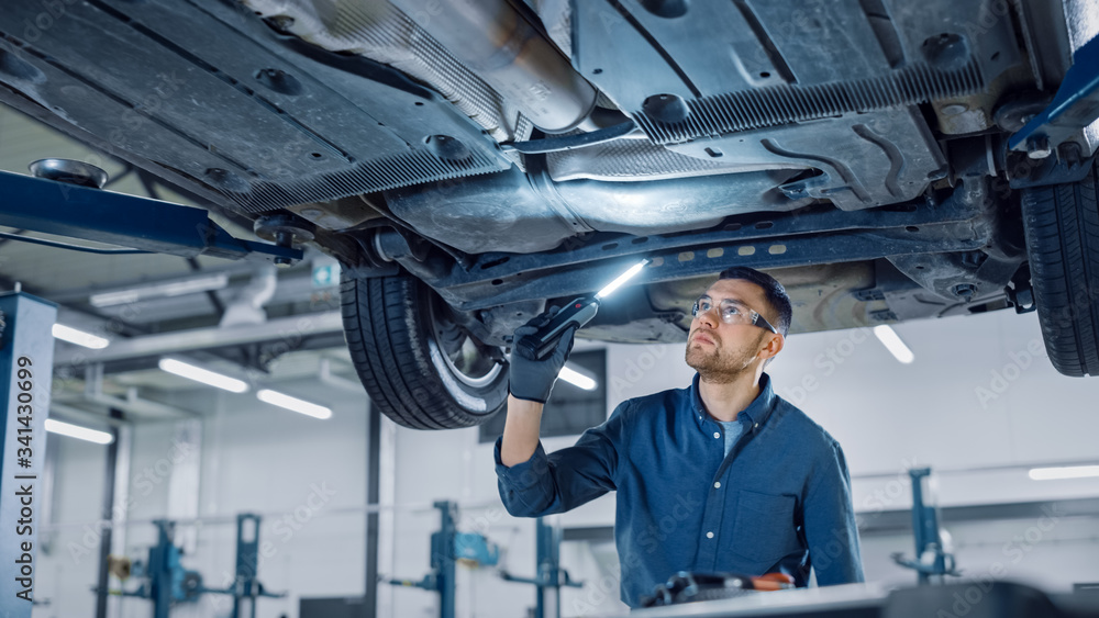 Fototapeta Handsome Professional Car Mechanic is Investigating Rust Under a Vehicle on a Lift in Service. Repairman is Using a LED lamp and Walks Towards. Specialist is Wearing Safety Glasses. Modern Workshop.