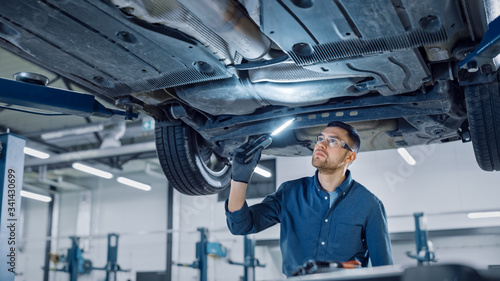 Fototapeta Handsome Professional Car Mechanic is Investigating Rust Under a Vehicle on a Lift in Service. Repairman is Using a LED lamp and Walks Towards. Specialist is Wearing Safety Glasses. Modern Workshop. obraz