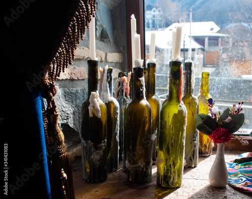 Leinwand Poster The image of white candles in glass wine bottles used as candlestick on window background