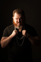 Angry Mid Adult Man With Beard Holding Chains Against Black Background