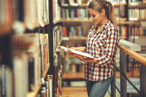 Leinwand Poster Young female student read and learns by the book shelf at the library