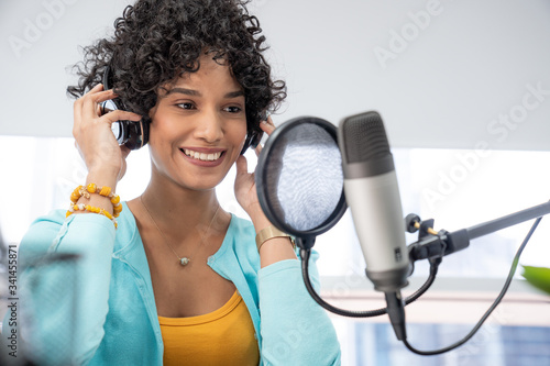 Fotografia, Obraz Good looking young black female making an online podcast recording