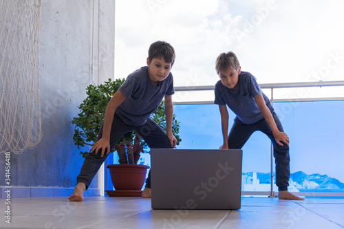Children with laptop doing sport exercises at home on balcony Canvas Print