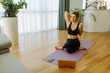Portrait of fit woman in black sportswear doing yoga on exercising mat at home. Young woman is following online yoga course due to COVID 19 pandemic.