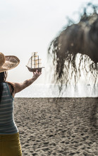 Woman In Hat Holding Toy Boat At Beach