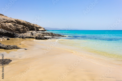 Fotografie, Obraz Crystal clear water beach by volcanic rocks coast on sunny day in Fuerteventura